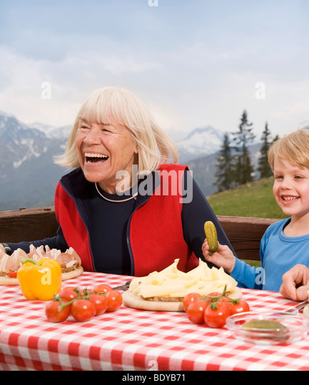 grandmother, grandson eating in mountain - Stock Image