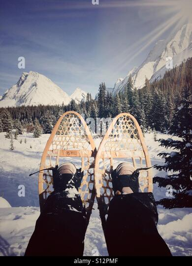 Resting while snowshoeing in the Rocky Mountains. - Stock Image