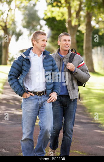 Two Male Friends Walking Outdoors In Autumn Park Together - Stock Image