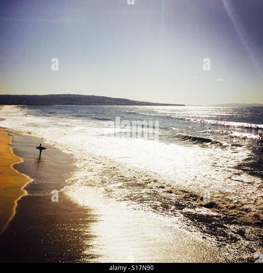 Surfer standing on the beach about to go surfing. Manhattan Beach, California USA. - Stock Image