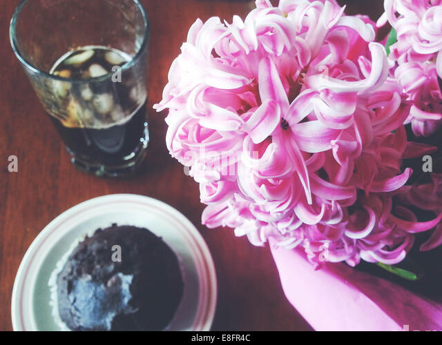 Chocolate muffin with ice coffee and hyacinth flowers - Stock Image