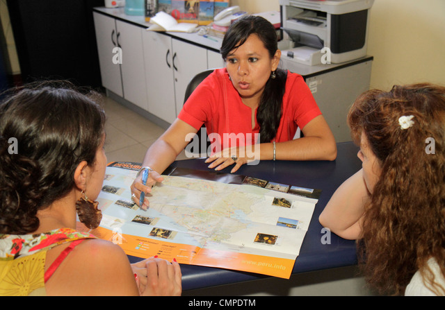 Peru Tacna Calle San Martin travel agency business sales Hispanic woman selling agent map visual aid speaking facial - Stock Image