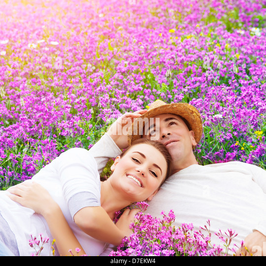 Young happy family laying down on fresh lavender meadow, hugging outdoors, summer season, romance and love concept - Stock-Bilder