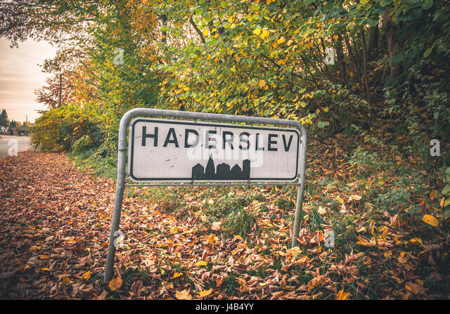 Haderslev city sign by a road in Denmark in the fall with colorful trees and leaves on the groubd - Stock Image