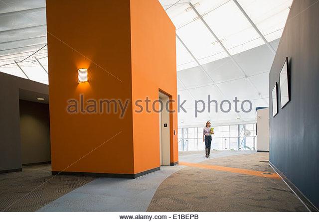 Woman walking in modern office corridor - Stock Image