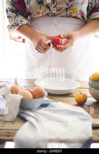 a woman in the kitchen peeling a fruit - Stock Image