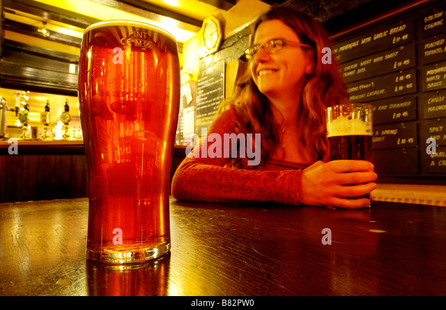 a-young-woman-smiling-and-holding-a-pint