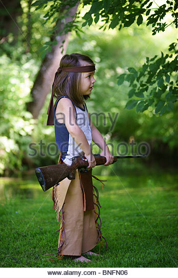 Little boy playing alone holding a real rifle dressed as a red indian - Stock Image