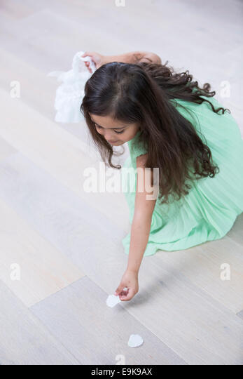 High angle view of girl picking up flower petals from floor at home - Stock Image