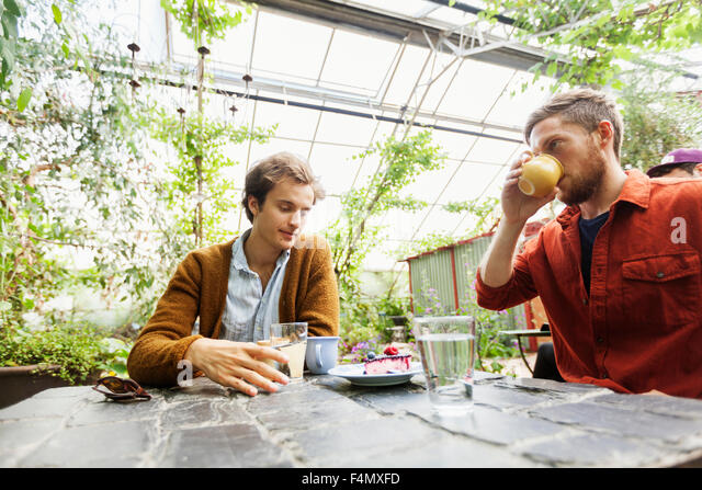 Men having coffee and cake on table at greenhouse - Stock-Bilder