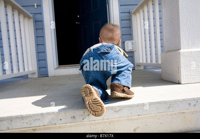 Child crawling towards open door - Stock Image