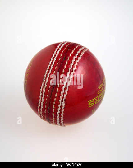 Sport, Ball Games, Cricket, Red hand stitched leather cricket ball on a white background. - Stock Image