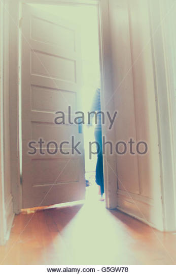 Figure exiting through a door - Stock Image
