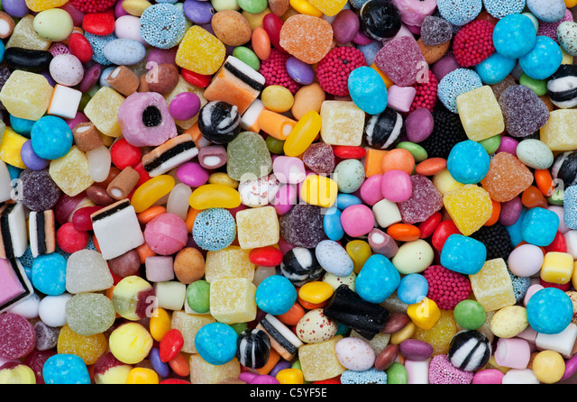 Colourful childrens sweets pattern. Liquorice allsorts, Smarties, pineapple cubes, humbugs, bonbons, dolly mixtures - Stock Image