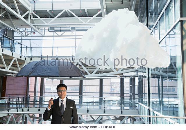 Portrait businessman with umbrella under cloud in atrium - Stock Image