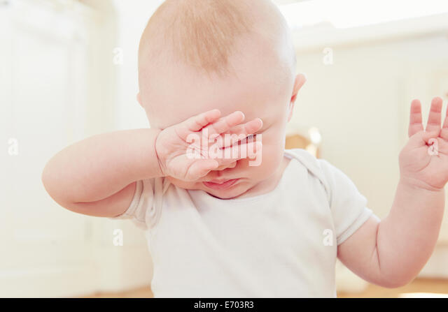 Close up of tired baby boy with hand covering eyes - Stock Image