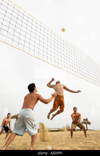 Man in Mid-air Going for Volleyball on beach - Stock Image
