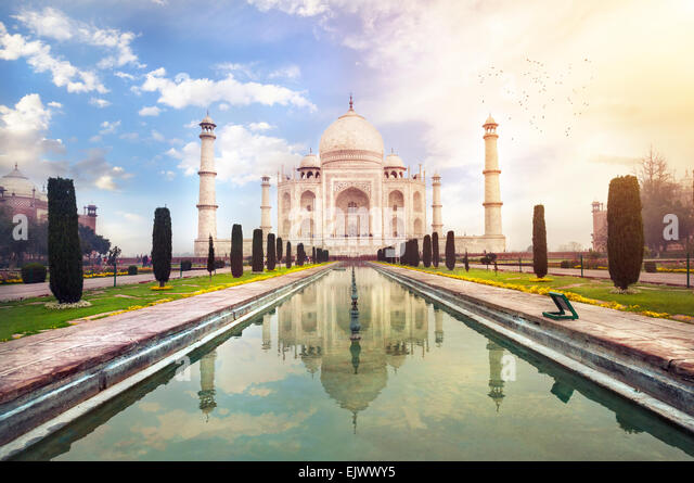 Taj Mahal tomb with reflection in the water at blue dramatic sky in Agra, Uttar Pradesh, India - Stock Image