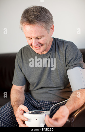 Man using blood pressure monitor - Stock Image