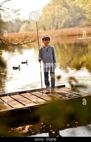Boy standing on pier holding fishing nets, portrait - Stock Image