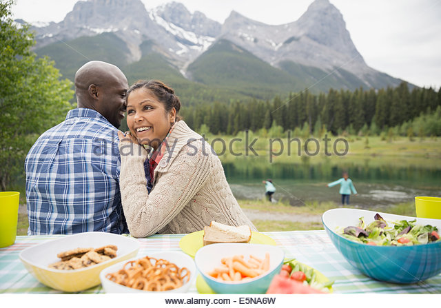 Couple sitting at picnic table near lake - Stock-Bilder