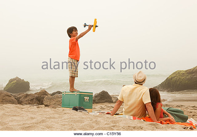 Family on beach, boy playing with toy plane - Stock-Bilder