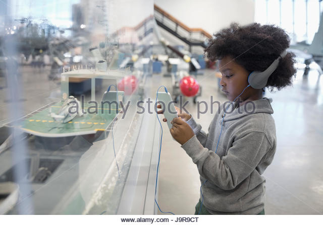 Curious African boy student wearing headphones and using digital tablet at exhibit on field trip in war museum - Stock-Bilder