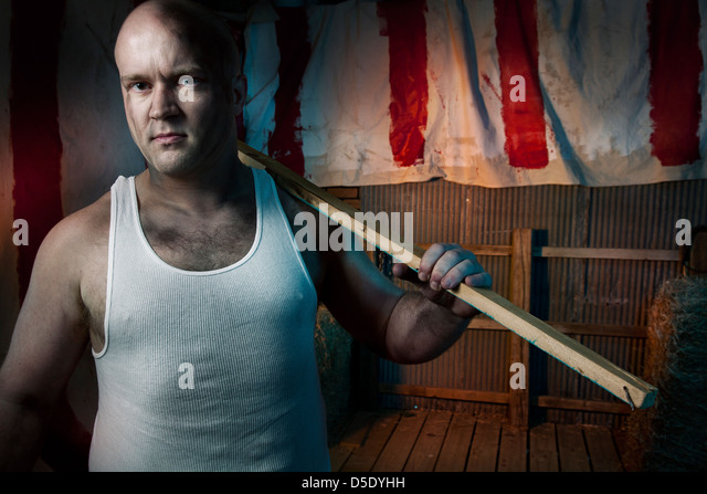 Man with board in front of dark tented alley - Stock Image