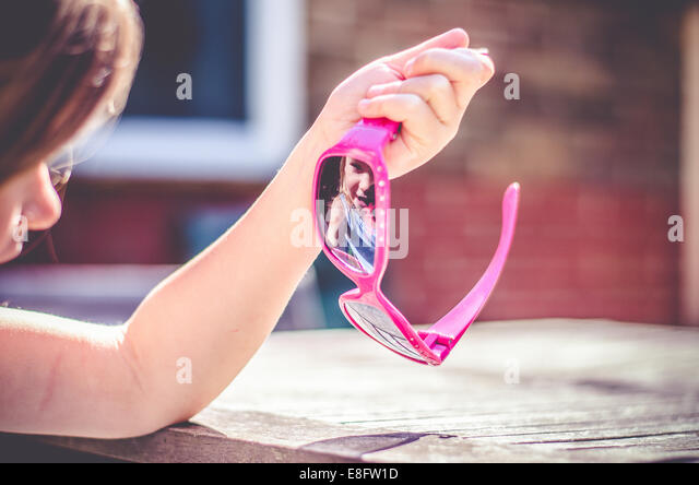 Girl looking at her reflection in her sunglasses - Stock Image