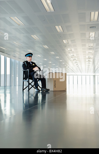 Uniformed guard sitting in empty office space - Stock Image