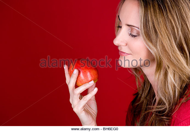 A mid adult woman holding an apple - Stock Image
