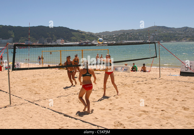 Four women playing beach volleyball, Oriental Bay, Wellington, New Zealand - Stock Image