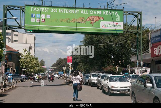 People and traffic on Kenyatta Avenue Nakuru Kenya East Africa with advertising hoarding for 3g Network   KENYATTA - Stock Image