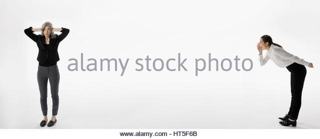 Businesswoman yelling at colleague covering ears against white background - Stock-Bilder
