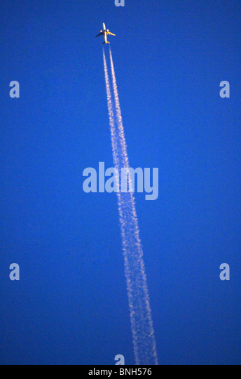 Aeroplane leaves contrails in the sky, jet plane leaving contrail - Stock Image