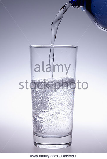 Mineral water pouring into glass - Stock Image