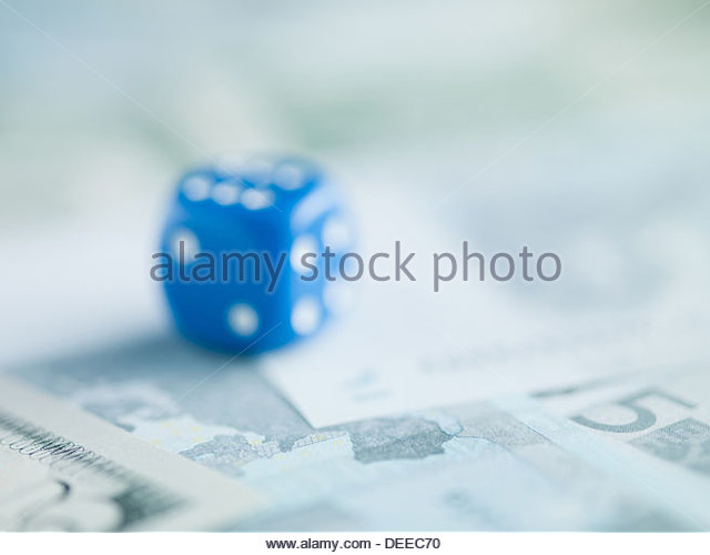 Blur blue dice on pile of dollar bills - Stock Image