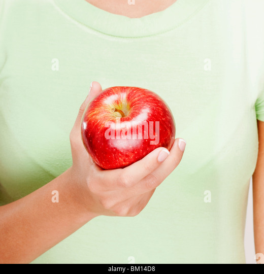 Mid section view of a woman holding a red apple - Stock-Bilder