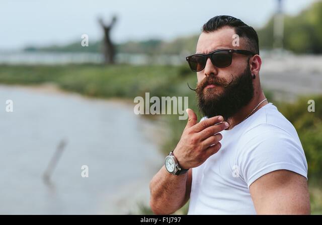 American Bearded Man touching his beard - Stock-Bilder