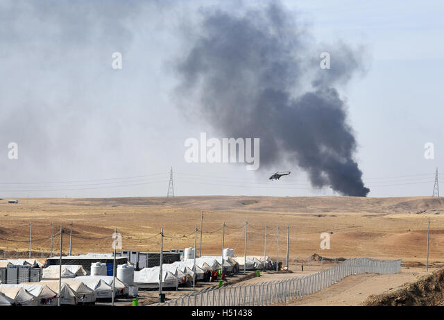 A helicopter and black smoke from a burning oil facility can be seen behind the Debaga refugee camp between Mosul - Stock-Bilder