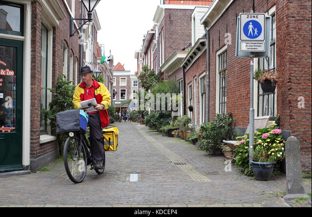 A postal worker delivering mail in a traffic-free street in Haarlem, The Netherlands. - Stock Image