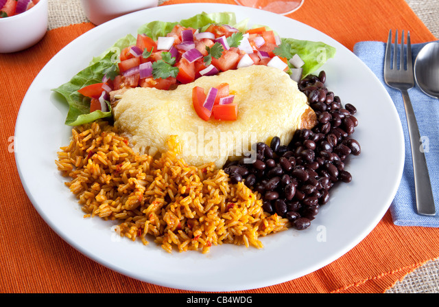 Burrito plate with a side of black beans rice and a fresh salad. - Stock Image