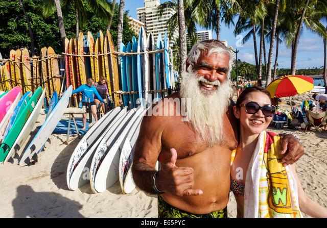 Hawaii Hawaiian Honolulu Waikiki Beach resort Kuhio Beach State Park man long white beard surfer Asian woman posing - Stock Image