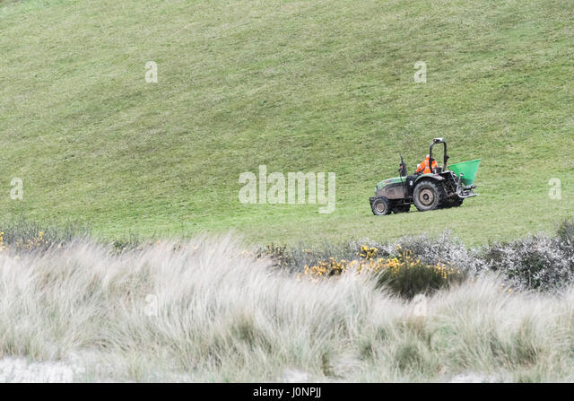 Distant shot of farm tractor with top dresser. - Stock Image
