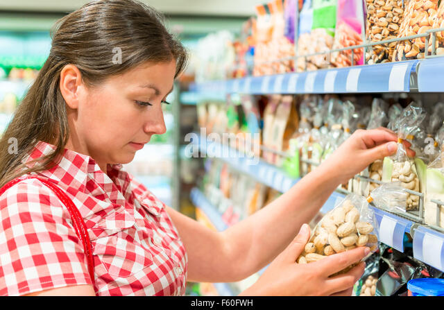 woman on the shelf at the store chooses the nuts - Stock Image