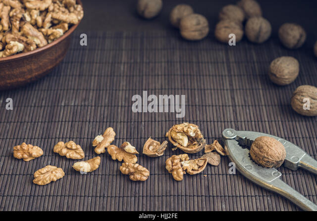 Walnut kernels and whole walnuts in brown ceramic bowl. Healthy organic food concept. Selective focus - Stock Image