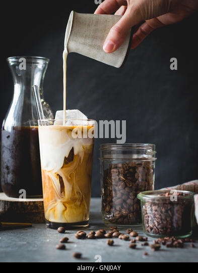 Woman pouring milk in to an iced coffee - Stock Image