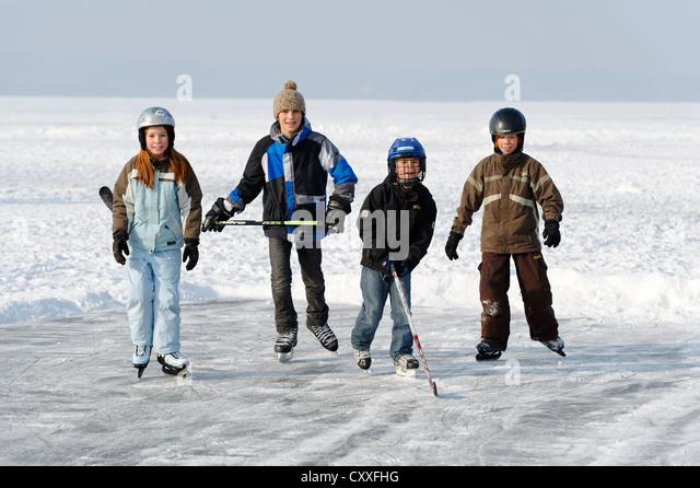 Children playing ice hockey, near St. Heinrich, Lake Starnberg, Five Lakes region, Upper Bavaria, Bavaria - Stock Image