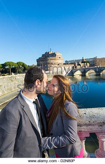 Couple on bridge Ponte Vittorio Emanuele in front of Castel sant'Angelo Rome Italy - Stock Image