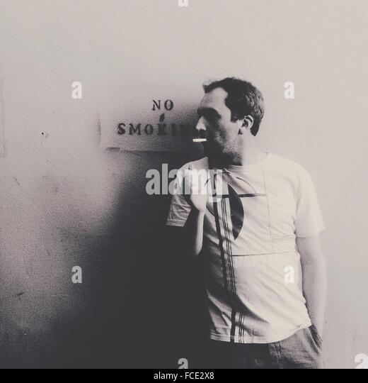 Man Smoking Against Warning Sign - Stock-Bilder